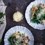 Three plates with fettucine boscaiola, a glass of wine, grater and parmasean