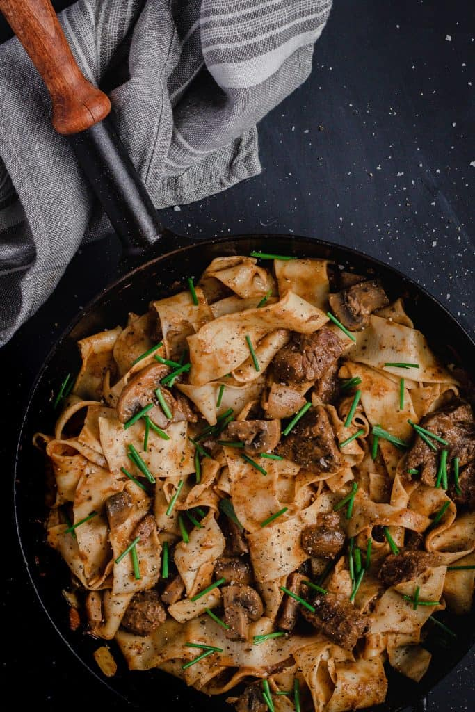 slow cooked beef stroganoff with black pepper parpadelle in a cast iron frypan