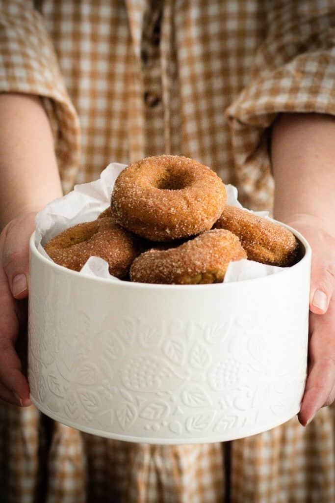 Cake tin full of baked apple cider doughnuts.