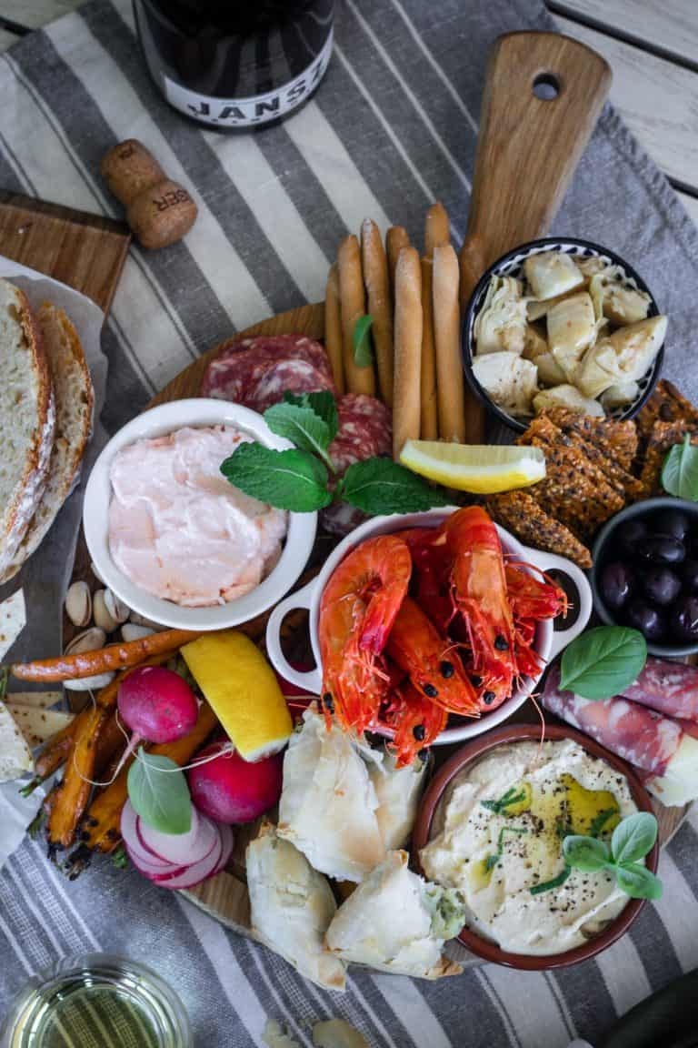 Round board full of meze. olives, dips, chargrilled vegetables, prawns, cured meats, breadsticks, crackers and sourdough.