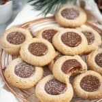 spiced dulce de leche thumbprints dusted with icing sugar on a copper cooling rack